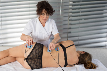 therapeutics: woman is doing massage of electrostimulator for the spine