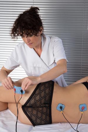 stimulator: woman is doing massage of electrostimulator for the spine