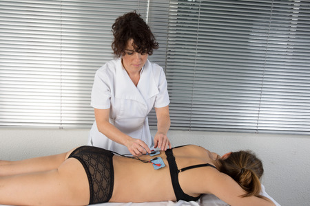 therapeutics: Woman is doing massage of electrostimulator for the spine Stock Photo