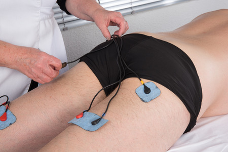 stimulator: A man doing a massage of the back of the thighs by electrode