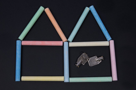 Two houses with keys from a chalk on a black board photo