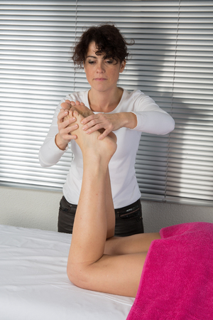 touching toes: Foot massage. Female hands giving massage to soft bare foot Stock Photo
