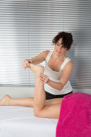 restore energy flow: Foot massage. Female hands giving massage to soft bare foot Stock Photo