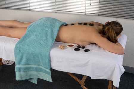 stone massage: Young woman having stone massage in spa salon. Healthy lifestyle Stock Photo