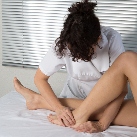 tuina: Foot massage. Female hands giving massage to soft bare foot Stock Photo