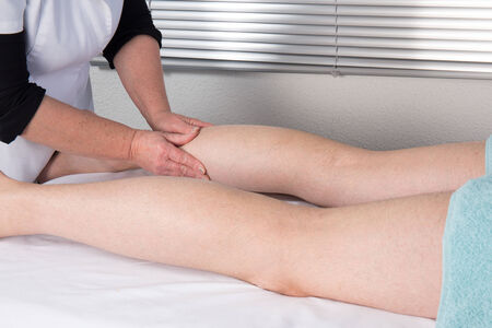 tuina: Side view of a man legs receiving a massage therapy