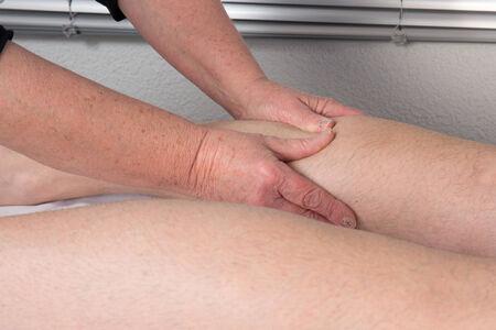 piernas hombre: Vista lateral de un hombre piernas recibiendo una terapia de masaje
