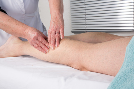 Side view of a man legs receiving a massage therapy photo