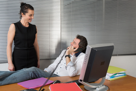 business man relaxing at office desk and talking on mobile phone Stock Photo