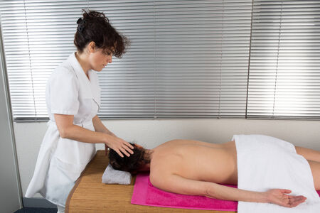 Therapist woman doing massage on a womans head