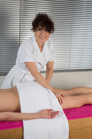 Side view of a woman legs receiving a massage therapy photo