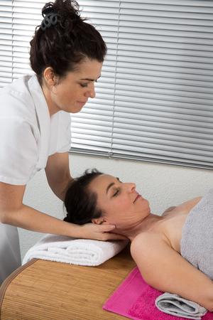 extending: Therapist woman doing massage on a womans head