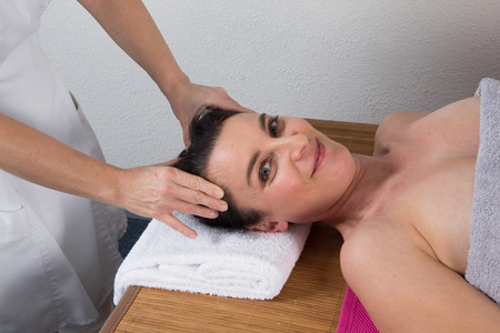 spirituality therapy: Therapist woman doing massage on a womans head