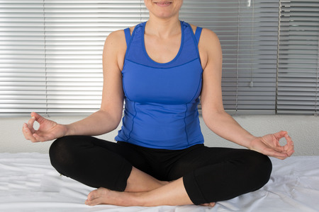 young woman meditating in pose of lotus. Yoga background