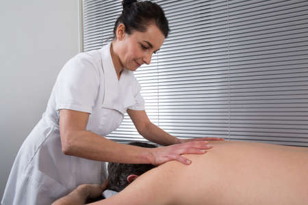 physical pressure: A physical therapist giving a back massage
