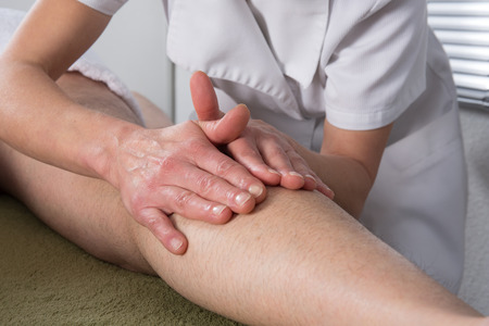 acupressure hands: A man receiving a ayurvedic massage on his legs Stock Photo