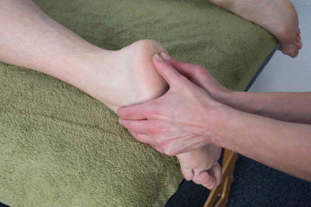 Chinese massage on mans feet photo