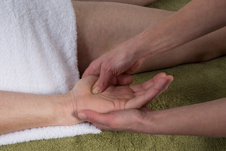 traditional healer: Woman doing a hand massage to a man in the spa salon