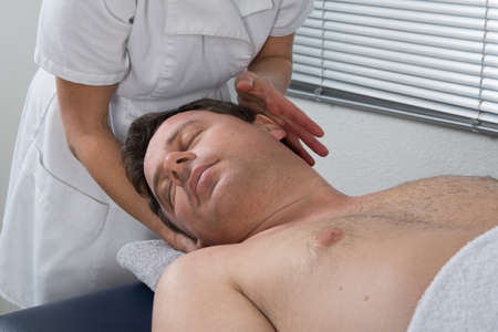 A woman spirit healer doing reiki treatment to a man photo