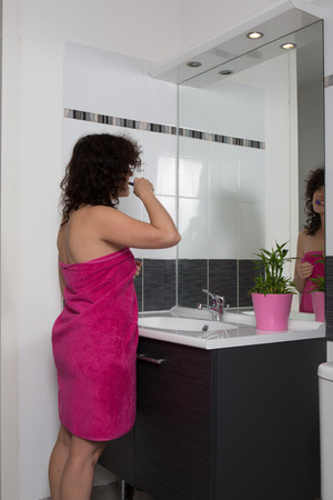 Woman with a bath towel around her chest brushing her teeth photo