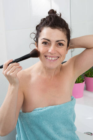 miror: Woman in her bathroom in the process of putting blush