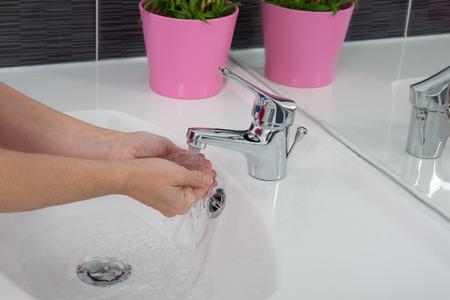 sump: Donna che si lava le mani sotto un getto d'acqua