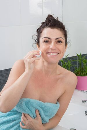 removing: Woman removing makeup with cotton bud Stock Photo