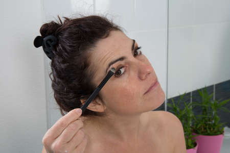 brush in: Woman face with mascara brush in a bathroom Stock Photo
