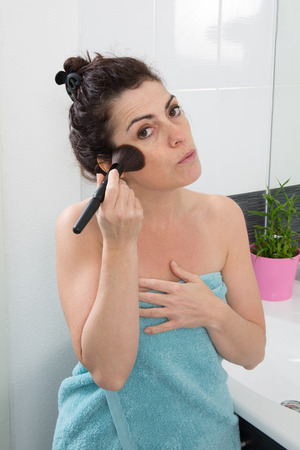 powder room: Woman in her bathroom in the process of putting blush
