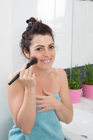 Woman in her bathroom in the process of putting blush photo