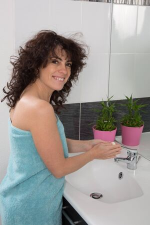 handwashing: Woman in bathroom washing her hands with soap