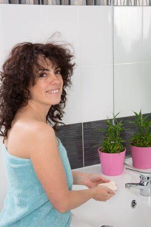 lavarse las manos: Mujer en el baño lavándose las manos con jabón