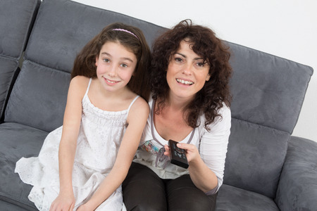 Portrait Of Mother And Daughter Sitting On Sofa At Home photo