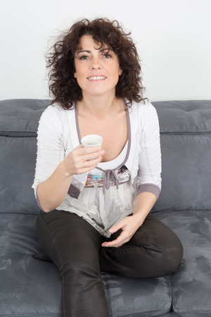 Casual woman on her couch at home drinking coffee photo