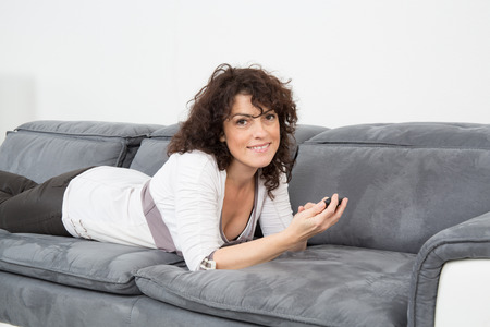 home comforts: Happy and nice woman relaxing on sofa Stock Photo