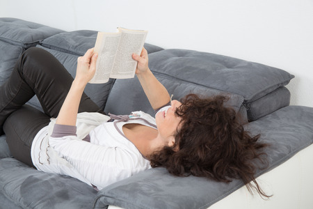Happy and nice woman relaxing on sofa Stock Photo