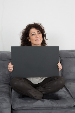 bill board: Casual woman on her couch holding black bill board Stock Photo