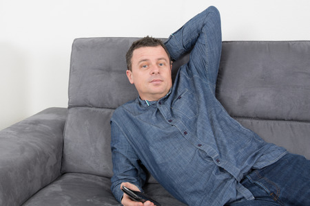 unsatisfactory: Man thinking on the sofa alone at home