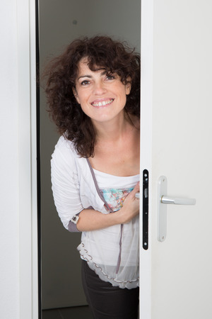 Nice caucasian woman standing near the door to open