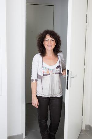 Nice caucasian woman standing near the door to open photo