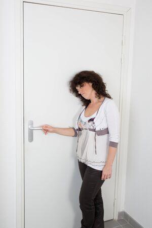 joyfull: Nice  brunette woman  behind the door, waiting