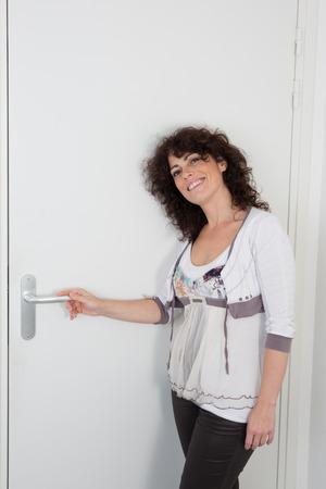 joyfull: Brunette woman  in front of the door, waiting