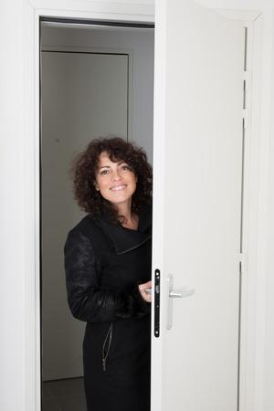 Woman In A Coat Walks Into A Room Through The Door Stock Photo