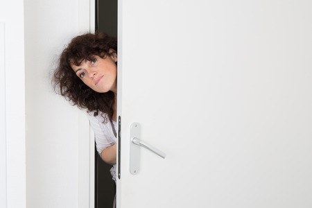 Nice caucasian woman peeking through door Stock Photo