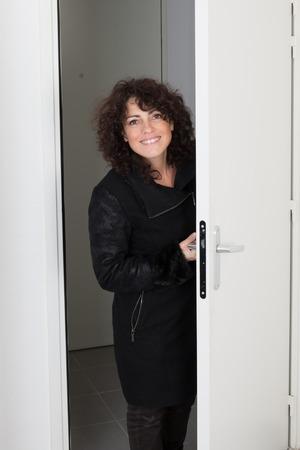 woman in a coat walks into a room through the door photo
