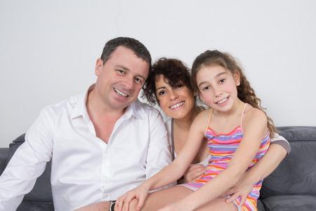 family sofa: Cheerful family sitting on their sofa