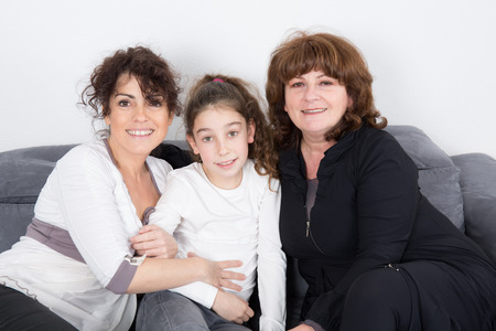Three generations of women smiling at camera and having fun