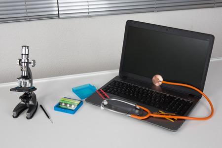 laptop with orange stethoscope on the grey background