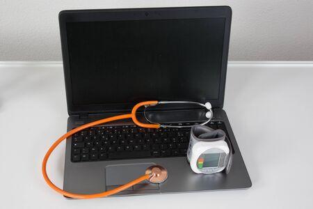 interception: laptop with orange stethoscope on the gray background Stock Photo