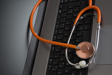 outpatient: laptop with orange stethoscope on the gray background Stock Photo